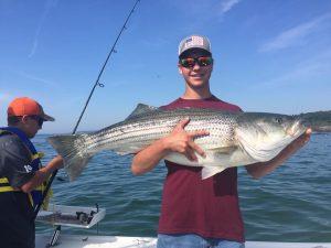 man holding striper fish